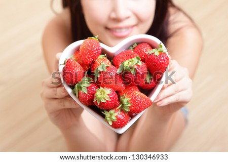strawberry - Woman smiling with strawberry on wooden floor background, focus on fruit, asian beauty model - stock photo