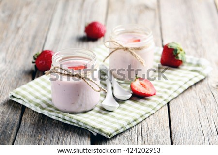Strawberry yogurt in glass on a grey wooden table - stock photo