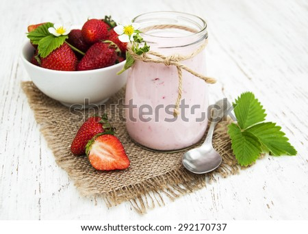 Strawberry yogurt with fresh strawberries on a wooden background - stock photo
