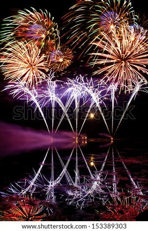 Streaks of Blue Fireworks reflected in a murky lake - stock photo