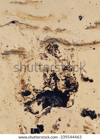 Streaks of Crude oil spilled on sand beach polluted seawater. - stock photo