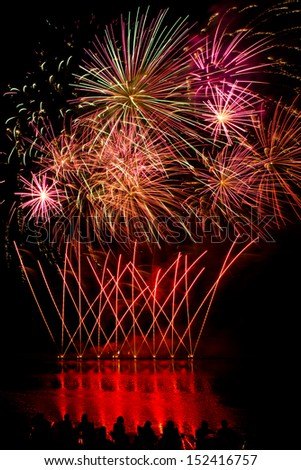 Streaks of Red Fireworks with people watching by a lake - stock photo