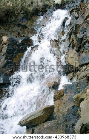 Stream among melting snow in a Carpathian Mountains - stock photo