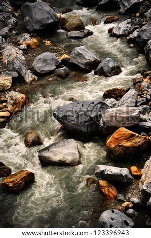 Stream flowing around tranquil rocks - stock photo