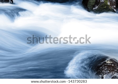 Stream flowing fast over rocks - stock photo