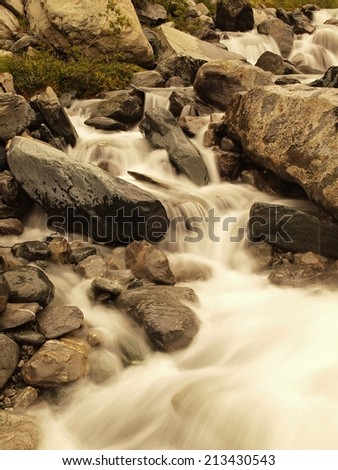 Stream flowing in motion over rocks. Blurred waves of Alpine  brook running over boulders and stones, reflections in the water level. - stock photo