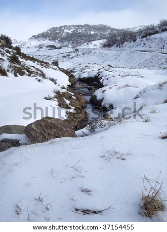 Stream of water amongst the snow - stock photo