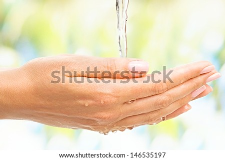 Stream of water pouring over the beautiful female hands - stock photo