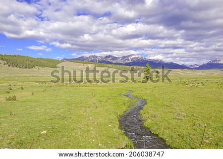Stream with Cloud filled sky over snow-capped mountains, Rocky Mountains - stock photo