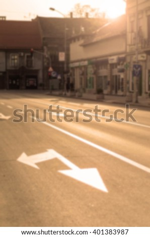 Street at sunset and arrows for turning on the road or asphalt, photo in soft focus - stock photo