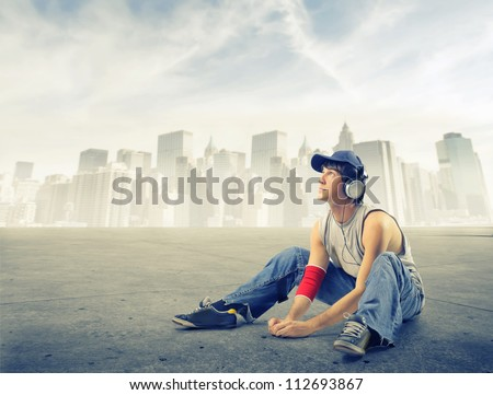 Street boy listening to the music on a ground near New York - stock photo