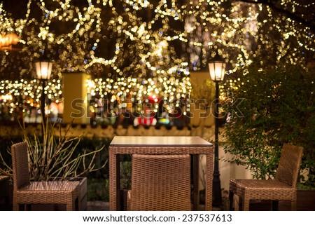 Street cafe at the night against city illumination lights - stock photo