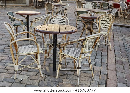Street cafe chairs tables on paving stones. Street cafe in old town - Riga, Latvia. - stock photo