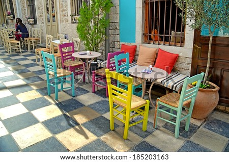 street cafe tables chairs  - ioannina athens city greece - road like chess - yellow blue pink colors - stock photo