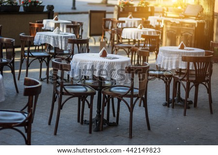 Street cafe terrace with wooden tables and chairs in European city - stock photo