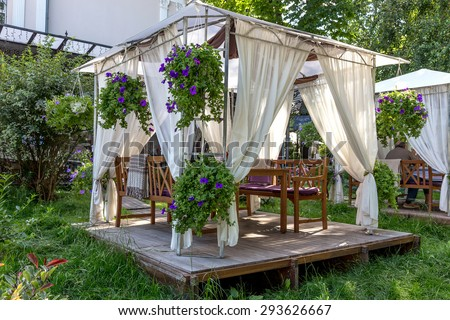 Street cafe under a canopy on a wooden platform located on the green with fresh grass in the city park and decorated with fresh flowers in Odessa - stock photo