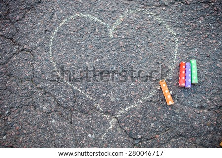 Street chalk drawing of a heart on asphalt - stock photo