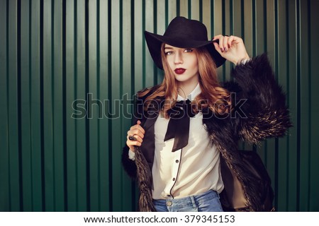 Street closeup portrait of a young beautiful lady wearing stylish black fur coat and wide-brimmed hat. Model looking at camera. Female fashion concept. Dark green background. Toned  - stock photo