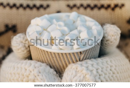 Street coffee with marshmallows in disposable cup in the woman hands in mittens  - stock photo