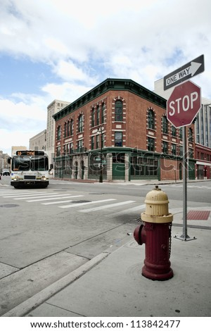Street corner in Detroit Michigan USA. A city bus in rounding the corner. - stock photo