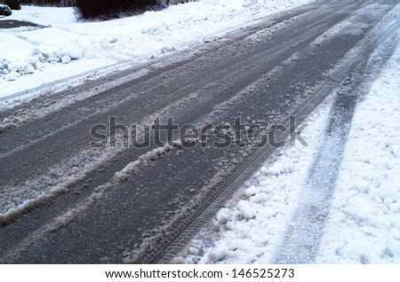 Street covered with car tires tracks and snow - stock photo