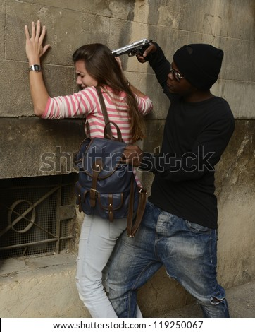 Street crime: Gang member with gun stealing backpack from girl - stock photo