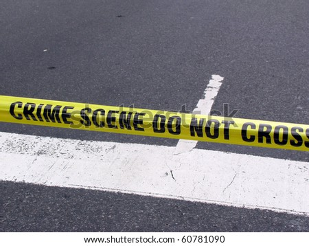 Street crime scene with police line do not cross yellow warning tape above road - stock photo