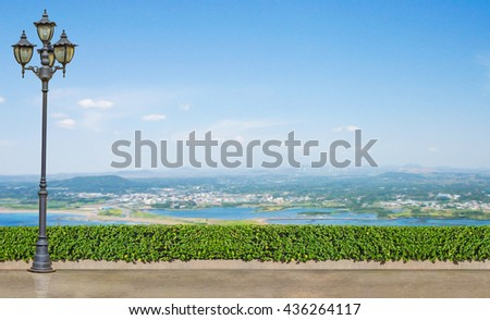 street electric lamp post at green tree bush fence on brown concrete floor side way with landscape of blue sky and city at blue sea on background - stock photo