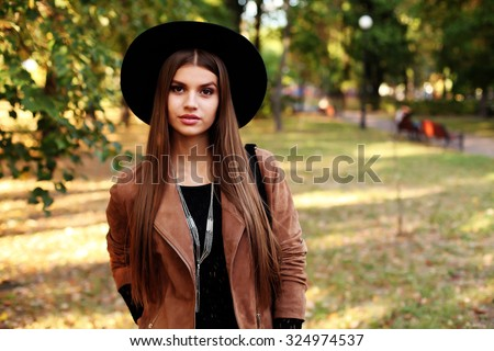Street fashion concept - closeup portrait of a pretty girl. Wearing hat and suede jacket holding bag with fringe. Beautiful autumn woman. Soft warm vintage color tone. Artsy bohemian style. Outside - stock photo