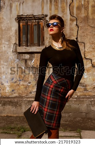 Street fashion concept. Fashion portrait of beautiful brunette in trendy casual clothes posing  over cracked wall. Vogue style. Outdoor shot - stock photo