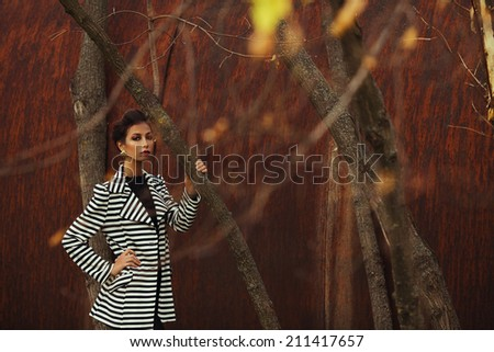 Street fashion concept. Fashion portrait of beautiful brunette in trendy casual clothes posing in autumn park over rusty metal background. Urban style. Outdoor shot - stock photo