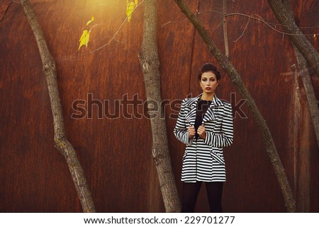Street fashion concept. Fashion portrait of beautiful brunette in trendy casual clothes posing in autumn park over rusty metal background. Stylish hairdo. Urban style. Outdoor shot - stock photo
