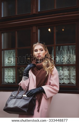 Street fashion concept: portrait of young beautiful woman wearing pink coat with handbag standing at the window - stock photo