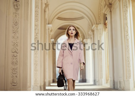Street fashion concept: portrait of young beautiful woman  wearing pink coat with handbag walking on old architecture background  - stock photo