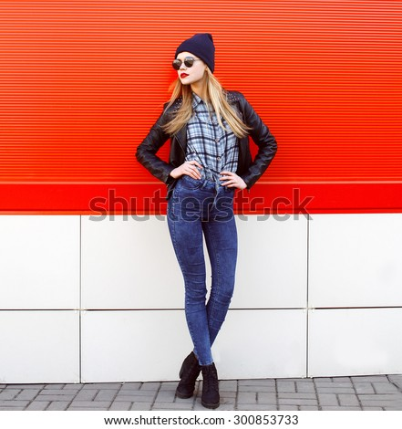Street fashion concept - pretty young slim woman in rock black style posing against the red wall - stock photo