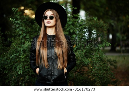 Street fashion concept - pretty young slim woman in rock black style, wearing stylish sunglasses and black leather jacket. Young cheerful fashion woman - stock photo