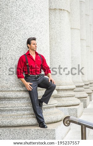 Street Fashion.  Wearing a long sleeve red shirt, trousers with suspenders,  a  handsome, strong, middle age businessman is standing against columns outside,  thinking.  - stock photo