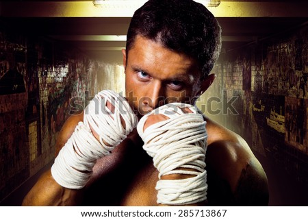 Street fighter muscular rack attack wrapped in his arms with ropes. Boxer on a background of the walls of the underpass - stock photo