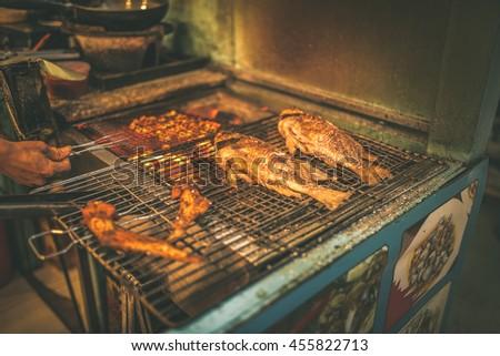 Street Food in Saigon, Vietnam. Hot fish on a grilling pan - stock photo