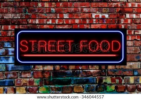Street Food Neon sign on a Graffiti. Bricks wall - stock photo