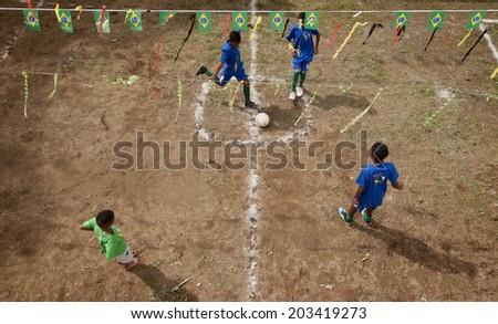 Street kids playing football, soccer, Rio de Janeiro, june 20, 2014 - stock photo
