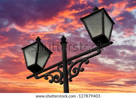Street lamnps on evening sunset sky background - stock photo
