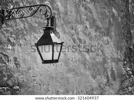 Street lamp hanging from the old wall - stock photo