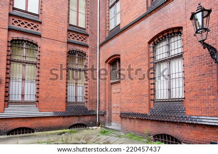 Street lamp on a brick wall of an old house in red - stock photo