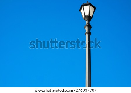 Street lamp on a bright blue background. Black lantern in vintage style, photographed in the morning sunshine. Bottom view. The object is to the right in the picture, the rest is free for your text. - stock photo