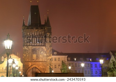 Street lamps and Gothic tower seen from the Charles bridge in foggy autumn night, Prague, Czech Republic - stock photo