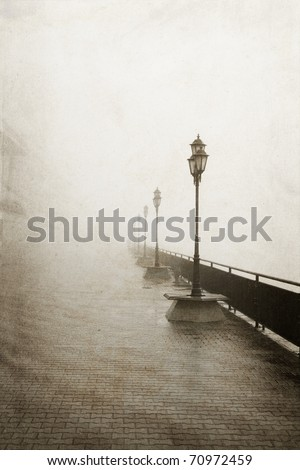 Street lamps in a fog. Photo in vintage image style. - stock photo