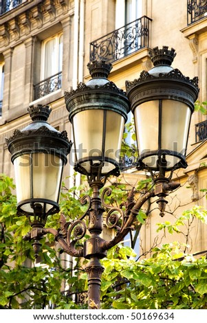 Street lamps with ornate ironwork in downtown Paris.  Traditional apartments with balconies are seen in the background. - stock photo