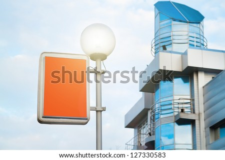 Street lantern with billboard on business building background - stock photo