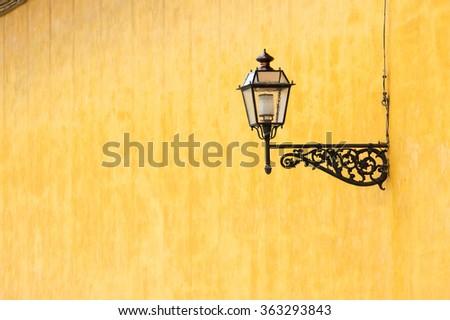 Street light on wrought iron bracket mounted on yellow wall - stock photo